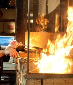 四国の漁師が獲れたて魚介を藁で焼く伝統の調理法を、店内で豪快にパフォーマンスしています。