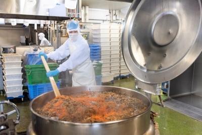 大釜での大量調理。一度に数千人分の量を、均一の味と品質に仕上げるよう配慮しながら作業します。