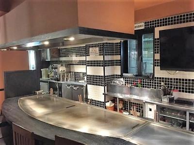 シックなデザインのオープンキッチンのお好み焼き店。お客様の反応を直接感じられます