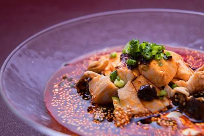 柔らかな蒸し鶏に自家製の辣油を合わせて。当店自慢のプレミアム蒸し鶏「四川名菜 よだれ鶏」。
